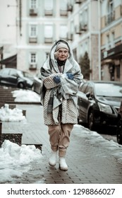 Cold city. Sad unhappy woman walking down the street while thinking about her life