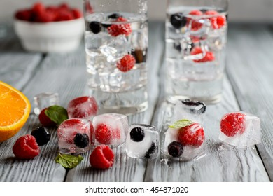 Cold cocktail with forest berries, frozen in ice cubes on wooden table