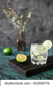 Cold cocktail with lime, tonic, vodka and ice on dark background