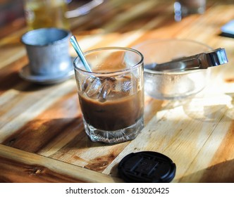 Cold Coffee cup with a bow of ice and coffee filter marker on the wooden table.