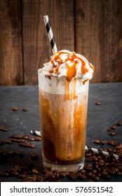 Boisson de café froid (frappuccino), avec crème fouettée et sirop de caramel, avec pailles et grains de café sur une table en pierre grise foncée, espace pour copie