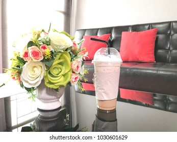 Cold coffee in a plastic glass placed next to a flower vase on the reception desk.