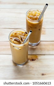 cold coffee with stainless steel straw on wooden table background.