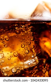 Cold cola drink with bubbles and ice cubes