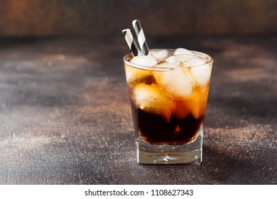 Cold Cola in glass with ice cubes on dark old concrete background.