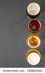 Cold craft beer assortment on a black background, top view. Overhead, from above. Copy space.