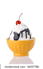 Cold and creamy hot fudge sundae with whipped cream and cherry in a bright yellow bowl