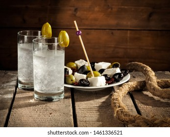 Cold crystal Ouzo with olive and cheese salad on wooden table, close up