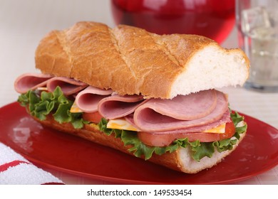 Cold cut sandwich with cheese, lettuce and tomato on french bread