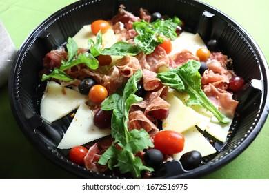 cold cuts, cheese, arugula, olive salad on a black bowl