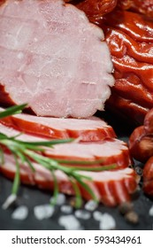Cold cuts on a stone board. Sliced sausage
