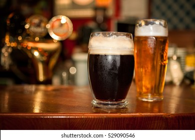 Cold dark beer with light beer in glasses