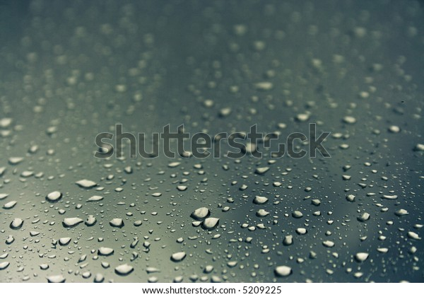 Cold dark-green water drops over glass background