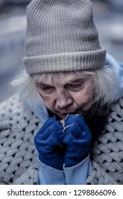 So cold. Depressed homeless woman trying to warm her hands while being outdoors