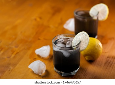 Cold detox lemonade with activated carbon on a wooden table