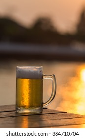 Cold Draught Beer with bokeh of the sunset in the sea background (Selective Focus Point)