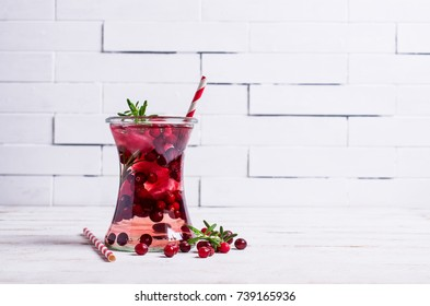 Cold drink with berries and ice in glass on wooden background. Selective focus.