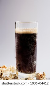 Cold drink with foam and popcorn, on a white background.