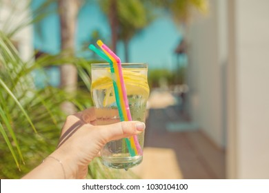 A cold drink with lemon is in the hands of a girl, close-up, a summer hot day