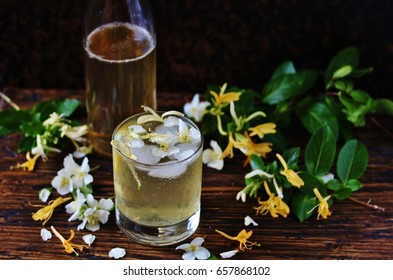 A cold drink of lemonade with syrup flowers of jasmine and honeysuckle. Syrup of jasmine flowers and honeysuckle. Unusual drinks from flowers and edible flowers.