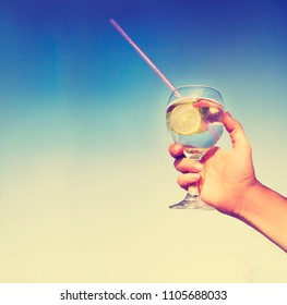 Cold drink with  slice of lemon in woman hand a hot summer day