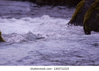 Cold fast flowing river with water droplets