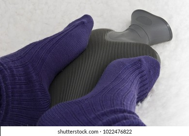 Cold feet with purple socks on a grey hot water bottle