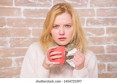Cold and flu remedies. Drink more liquid get rid of cold. Drinking plenty fluid important for ensuring speedy recovery from cold. Girl hold tea mug and tissue. Runny nose and other symptoms of cold.
