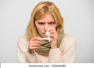 Cold and flu remedies. High temperature concept. Take temperature and assess symptoms. Measure temperature. Woman feels badly ill sneezing. Girl in scarf hold thermometer and tissue close up.