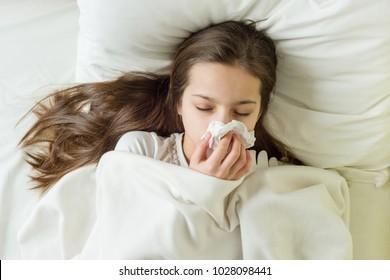 Cold flu season, runny nose. Sick girl on bed sneezing in handkerchief in bedroom