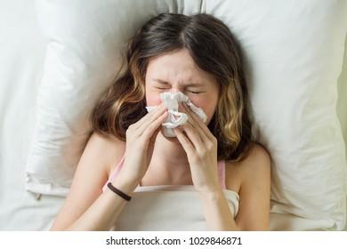 Cold flu season, runny nose. Sick girl on bed sneezing in handkerchief in bedroom.