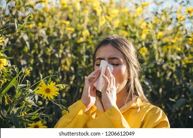 Cold flu season, runny nose. Flowering trees in background. Young girl sneezing and holding paper tissue in one hand and flower bouquet in other. Flu. Allergy season