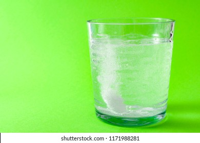 Cold and flu treatment and headache medicine concept with a effervescent aspirin dropped in a glass of water surrounded by fizzy bubbles isolated on green background with copy space for text