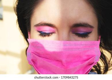 geschlossene Augenfrau mit rosafarbener Maske