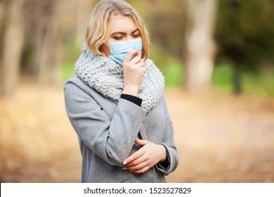 Cold and flu. Woman with a medical face mask at outdoor in autumn forest