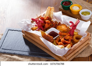 Cold Foamy Golden Chilled Glass of Draft Beer Served with Delicious Hot Crispy Homemade Fresh Fried Plate in Chicken Wings, Sliced Pork Saussage, Fries, Onion Rings and Cheese Stuffed Filo Dough Roll.