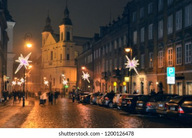 A cold, foggy, rainy December evening in the Warsaw Old Town, Poland. Christmas decorations on the street. Blurred image, out of focus