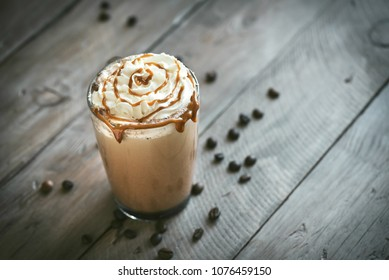 Cold Frappe Coffee with whipped cream and caramel syrop on dark background, copy space.