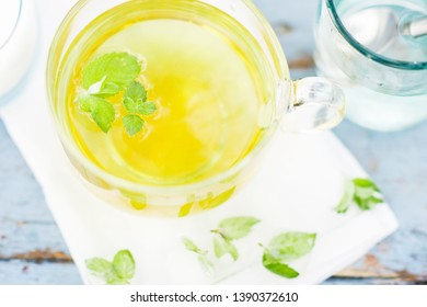 Cold fresh mint leaf tea, mint tea with ice cubes in a glass cup on a wooden table, cold mint beverage, healthcare and healthy eating concept