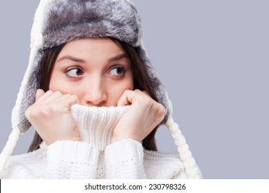 It is so cold. Frozen young women covering face with turtleneck while standing against grey background