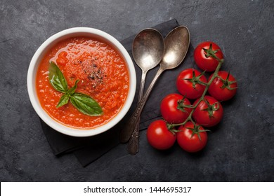 Cold gazpacho soup with ripe tomatoes, cucumber and basil on stone table. Top view flat lay