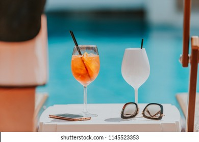Cold glass of aperol spritz on a pool side with blue water in summer, traditional Italian aperitif cocktail