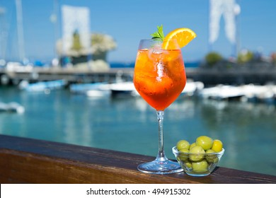 Cold glass of aperol spritz wit olive appetizer stand near the sea and boats