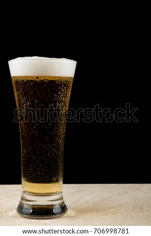 Cold glass of beer with water droplets on