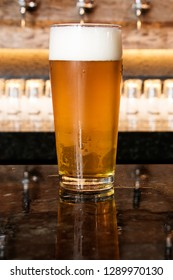 A cold glass of craft beer over a pub table with bokeh background. Happy hour time.