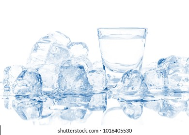 Cold glass of vodka in ice cubes on white background.