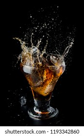 Cold glass with whiskey splash on a black background. Dark alcohol beverage.