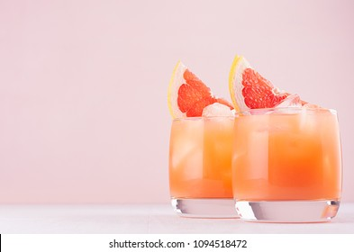 Cold grapefruit cocktail in two glasses with ice and pieces grapefruit on pastel pink background. Fresh summer healthy diet beverage.