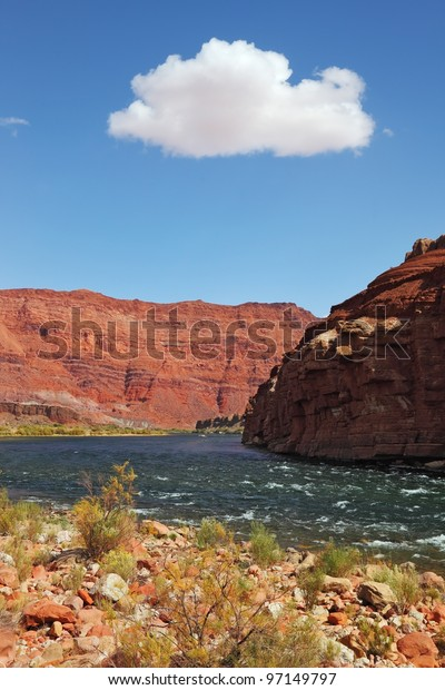 Cold green water in the shallows of the Colorado River in the red rocks of the desert