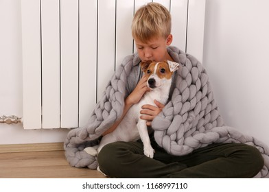 Cold home, freezing kid Wrapped In Blanket Sitting Near Heater with his dog